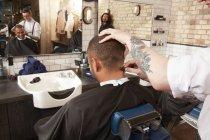Barbiere taglio clienti capelli in barbiere — Foto stock