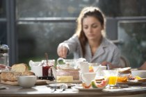 Женщина, сидящая на обеденный стол — стоковое фото