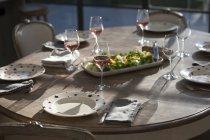 Salat und Wein am Esstisch — Stockfoto