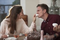 Woman feeding boyfriend with marshmallow — Stock Photo