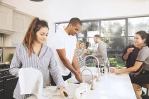 Friends washing dishes together — Stock Photo