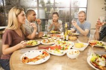 Friends eating dinner together — Stock Photo