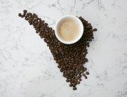 Чашка кави та кавових зерен — стокове фото