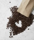 Coffee beans and paper bag with heart shape — Stock Photo