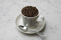 Grains de café dans la tasse à café — Photo de stock