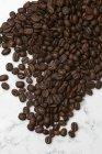 Chicchi di caffè su marmo — Foto stock