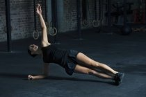 Woman exercising in side plank pose — Stock Photo