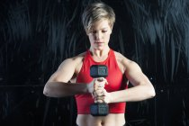 Woman using dumbbell in gym — Stock Photo
