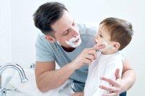 Père et fils utilisant la crème à raser — Photo de stock