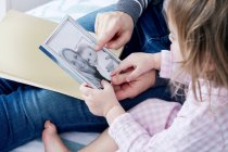 Mother showing photographs to daughter — Stock Photo