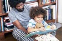 Отец с сыном читает книгу — стоковое фото