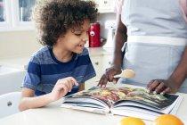 Отец и сын смотрят книгу рецептов — стоковое фото