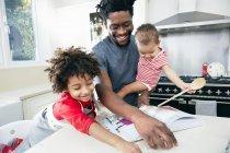 Vater mit Baby auf Hände betrachten Rezeptbuch — Stockfoto