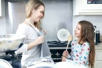 Mother putting apron on with daughter — Stock Photo