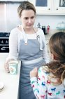 Mother and daughter talking in kitchen — Stock Photo