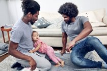 Fathers playing with daughter on rug — Stock Photo