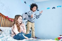 Children having fun on bed — Stock Photo