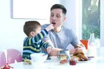 Father and son at dinner table — Stock Photo