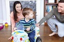 Rapaz em motocicleta em miniatura, com os pais — Fotografia de Stock