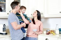 Father holding son in hands in kitchen — Stock Photo