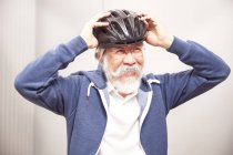 Man putting on bicycle helmet — Stock Photo