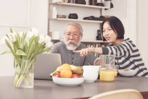 Senior pareja con portátil en la mesa del desayuno - foto de stock