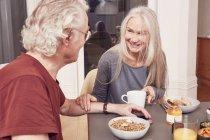 Coppia anziana seduta al tavolo della colazione — Foto stock