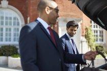Geschäftsleute, die entladen Gepäck aus dem Auto — Stockfoto