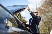 Бизнесмен выгружает багаж из машины — стоковое фото