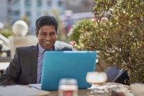 Hombre de negocios con ordenador portátil en el café - foto de stock
