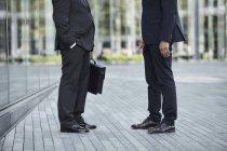 Pernas de homens de negócios falando no parque — Fotografia de Stock