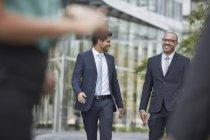 Smiling businessmen walking together — Stock Photo