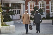Geschäftsleute gehen gemeinsam zum Hoteleingang — Stockfoto