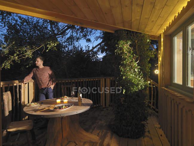 Homem de pé na varanda da cabine log — Fotografia de Stock