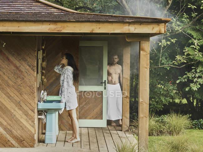 Женщина смотрит на себя в зеркало в ванной — стоковое фото