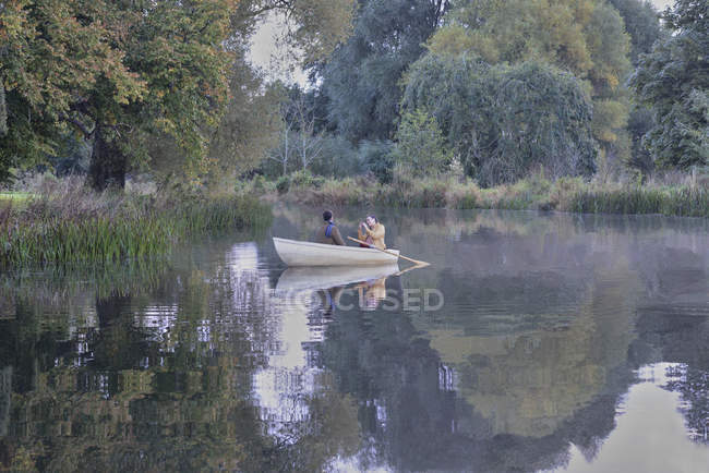 Woman taking photograph of boyfriend in rowboat — Stock Photo