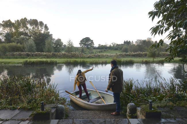 Uomo che aiuta la ragazza fuori barca a remi — Foto stock