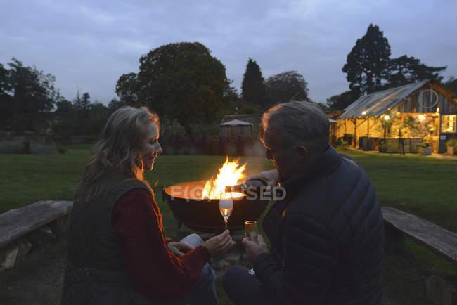 Муж и жена, пить вино у костра — стоковое фото