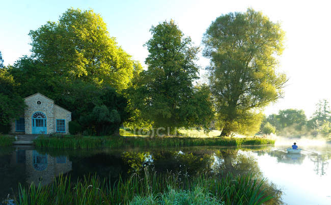 Riverside house and man in rowboat — Stock Photo