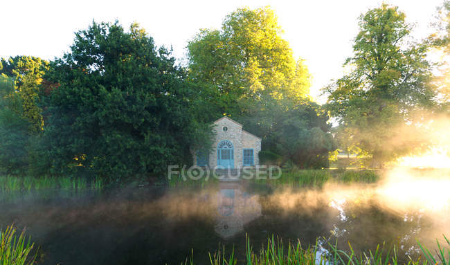 Riverside house at sunrise — Stock Photo