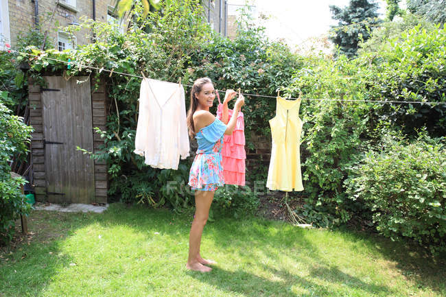 Young woman hanging washed clothing — Stock Photo