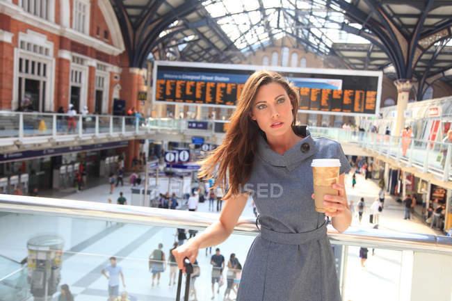 Junge Frau mit Tasse am Bahnhof — Stockfoto