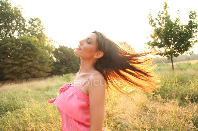Young woman in dress posing in field — Stock Photo