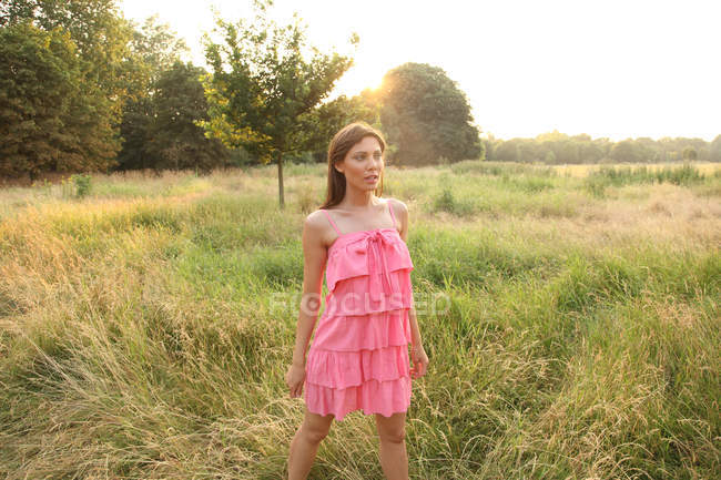 Young woman in dress standing in field — Stock Photo