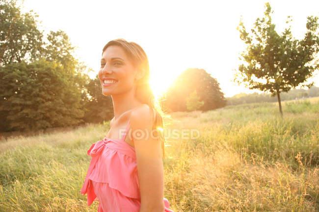 Молодая женщина в платье позирует в поле — стоковое фото
