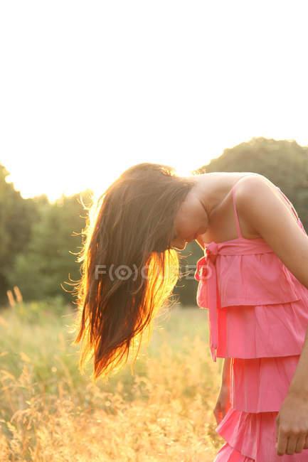 Junge Frau wirft Haare in Feld — Stockfoto