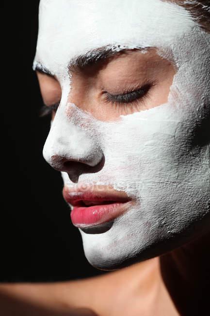 Donna che indossa maschera viso di crema bianca — Foto stock