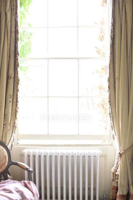 Radiador blanco debajo de ventana - foto de stock