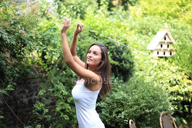 Женщина притворяется повешенной стиральной одеждой — стоковое фото