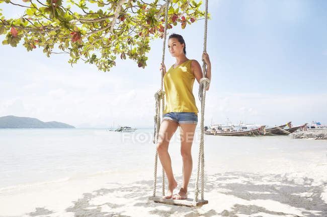 Woman standing on swing at beach — Stock Photo